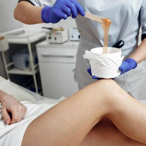 esthetician providing patient with body waxing services